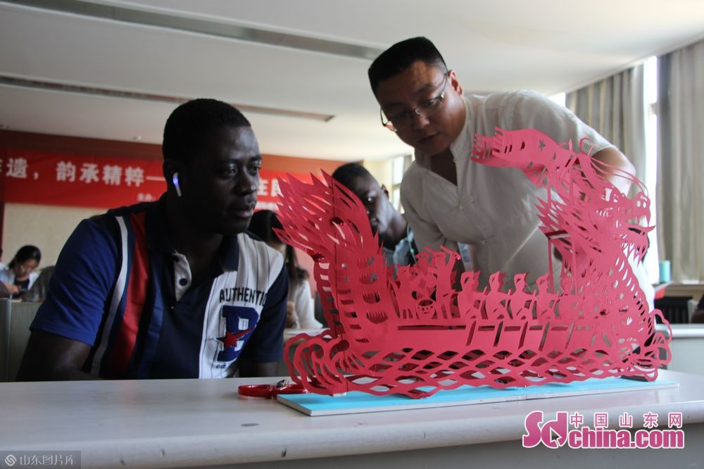 Wang Tao explains the cutting techniques of the dragon boat.<br/>