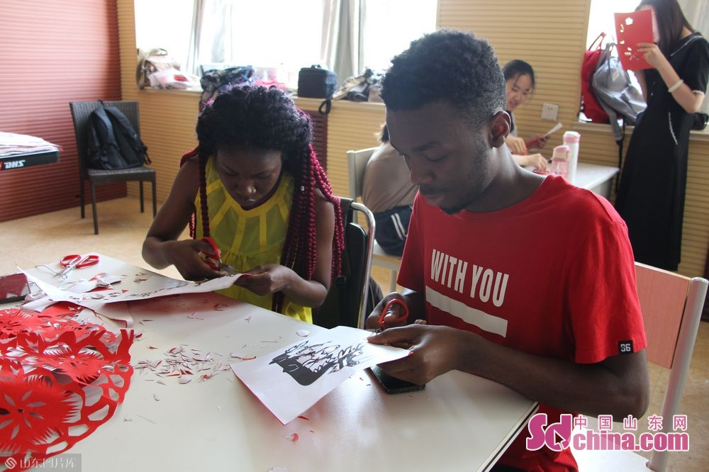 Foreign students learn to cut paper-cut works.<br/>
