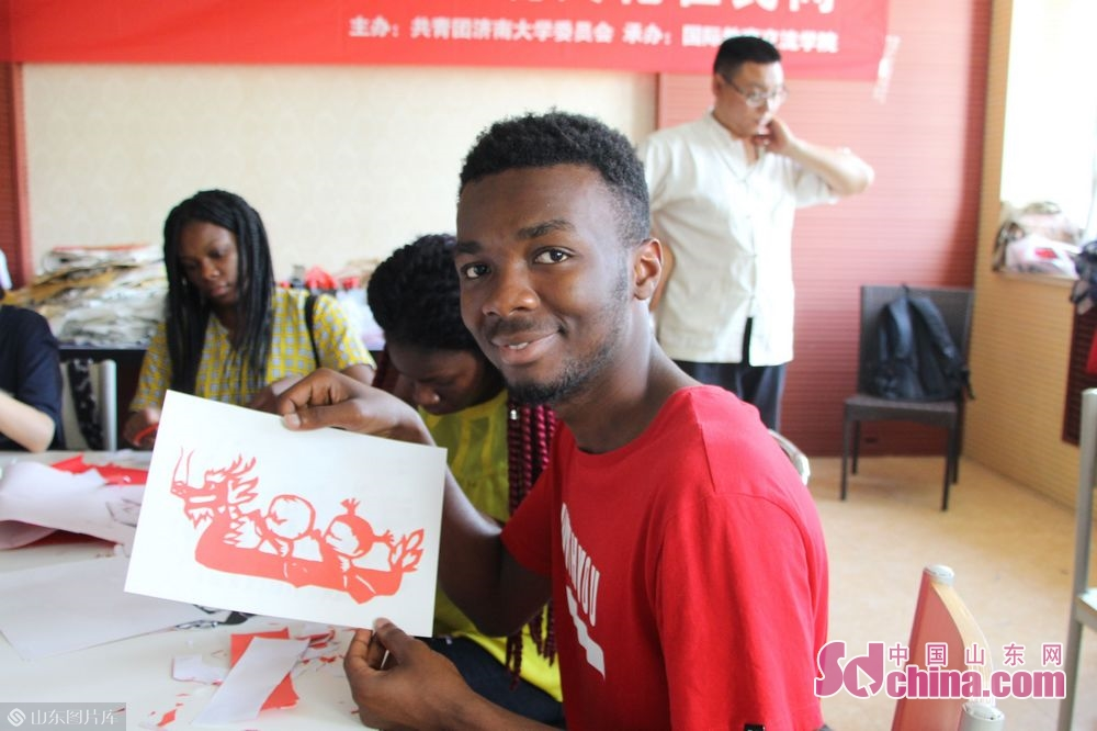 A foreign student shows his paper-cut work.<br/>