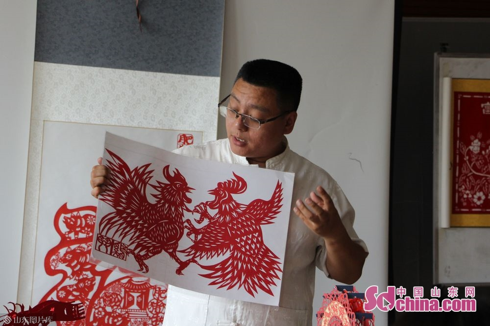 Wang Tao, an inheritance of Jinan style paper-cuts, is the president of Jinan Paper-cutting Art Institute. He gives an introduction of his paper-cut work.<br/>