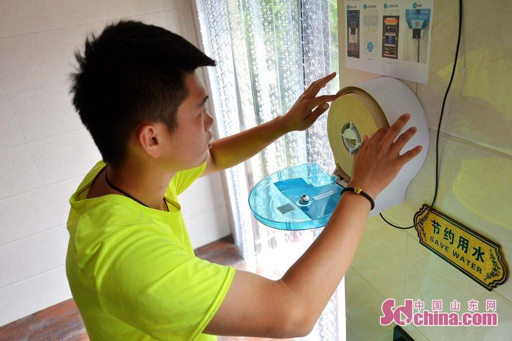 <br/>  7月12日,在山东省青岛市市北区北岭山森林公园,保洁人员为智能出纸机安放卷纸。<br/>