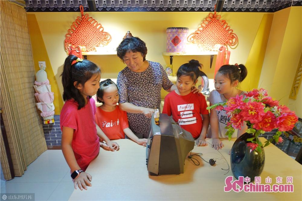 <br/>  2019年8月13日,孩子们在山东青岛水清沟街道民俗展览馆观看老物件黑白电视机。<br/>