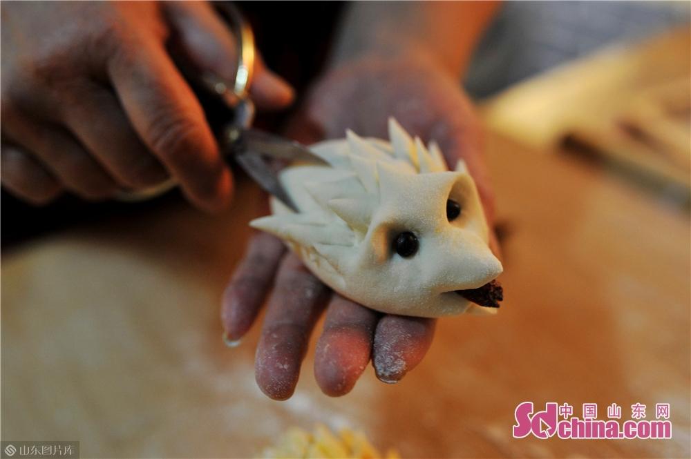 <br/>  2019年8月13日,民俗艺人在山东青岛水清沟街道民俗展览馆向孩子们展示胶东传统面塑&ldquo;刺猬&rdquo;的制作方法。<br/>
