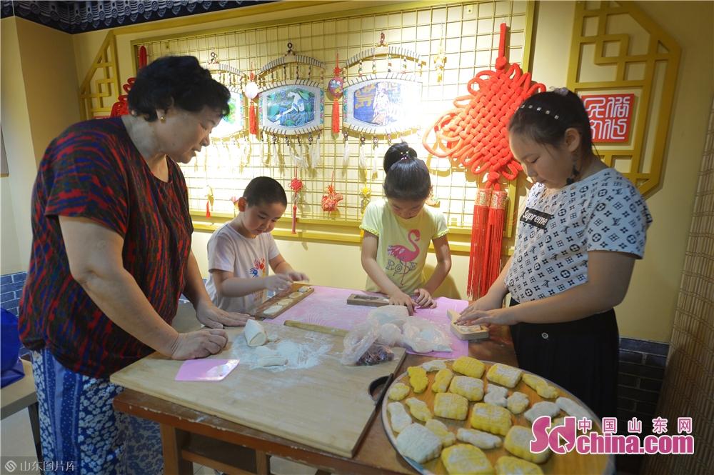 <br/>  2019年8月13日,孩子们在山东青岛水清沟街道民俗展览馆学习体验制作传统手工面点。<br/>