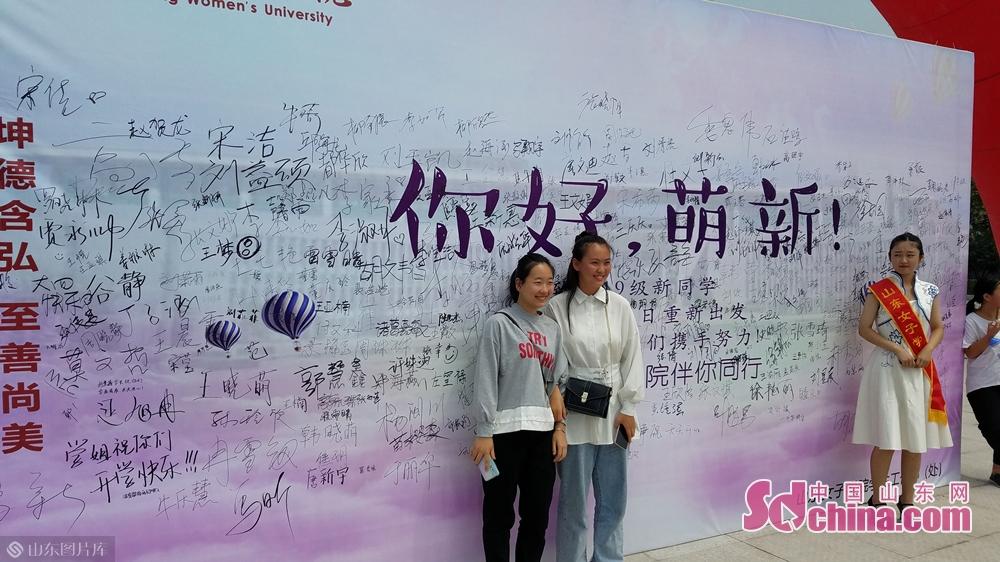 新同学在签名墙前合影。<br/>