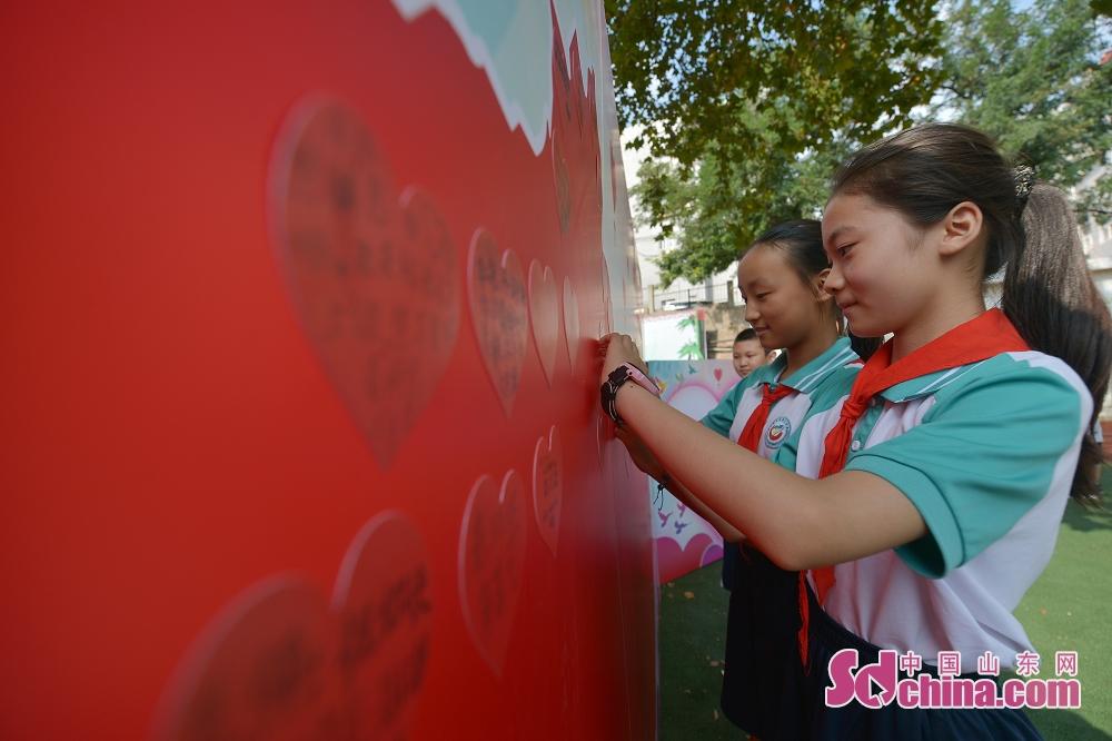 <br/>  9月9日,山东青岛重庆路第三小学的孩子们在中国地图牌板前粘贴爱心卡片送感谢师恩。