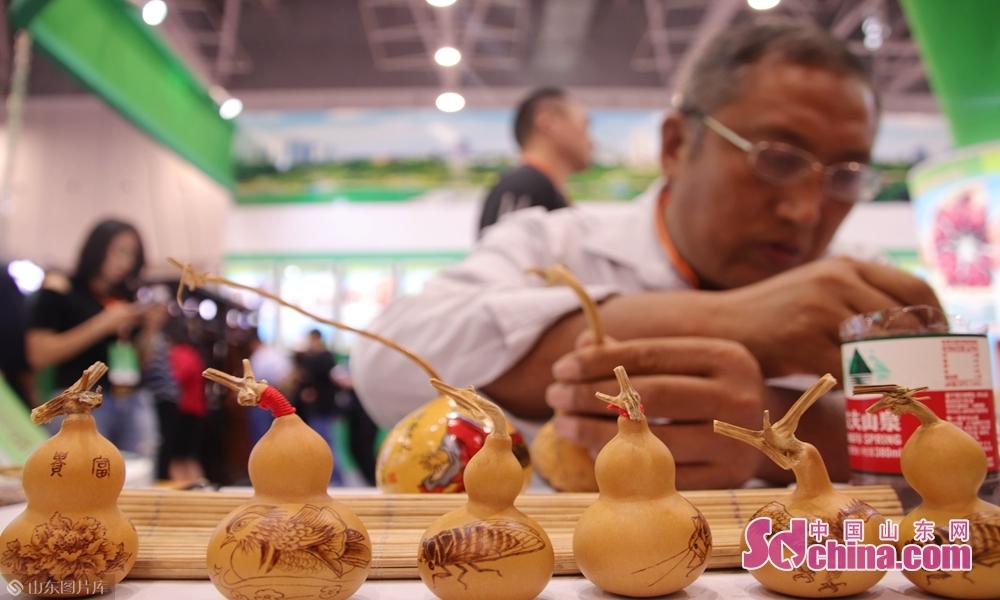 9月19日,山东菏泽第十六届林产品交易会现场,非物质文化遗产传承人王玉金与他的蒙山葫芦画作品。