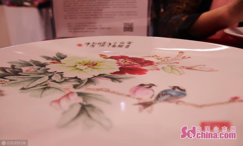 9月19日,山东省工艺美术大师马宪荣制作的刻瓷牡丹在山东菏泽第十六届林产品交易会现场展出。