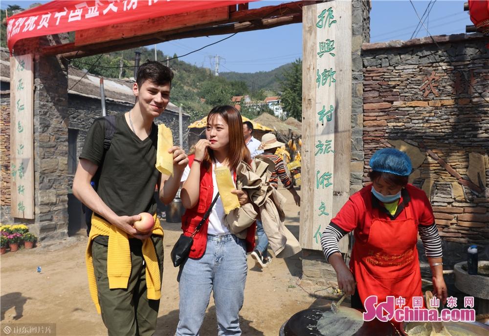 陽三峪村に入ると、金色のとうもろこし、白い落花生は留学生の目に見えた。村民は煎餅を作っていて、煎餅の香りが美味しそうだった。留学生は煎餅を食べてみて、「写真を撮って母にメールしたいです。この喜びをシェアします」とある留学生は言った。