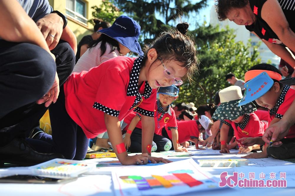 <br/>  9月27日,青岛市北区通榆路幼儿园的小朋友与社区居民在百米长卷上挥毫泼墨。<br/>