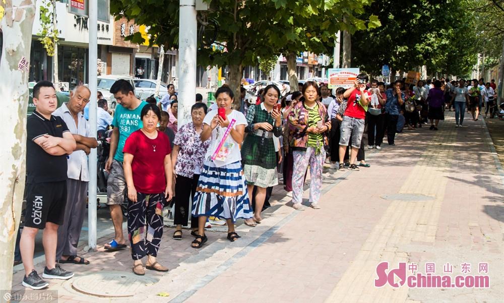 9月4号上午山东菏泽在八一路小学学校门口排队等候孩子放学的家长们。