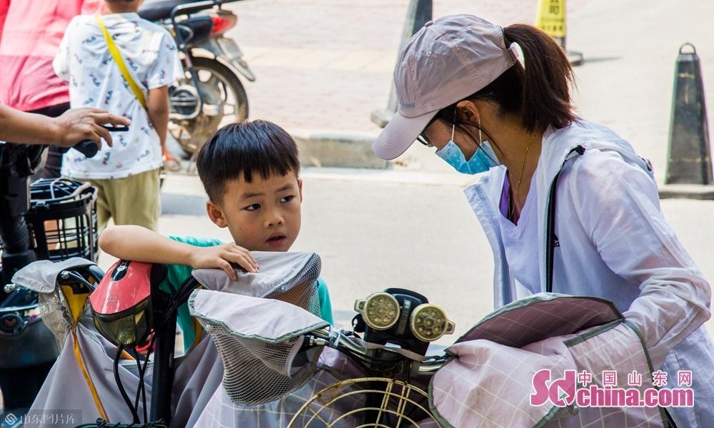 9月4号上午山东菏泽八一路小学家长与放学的孩子交流学习状况。