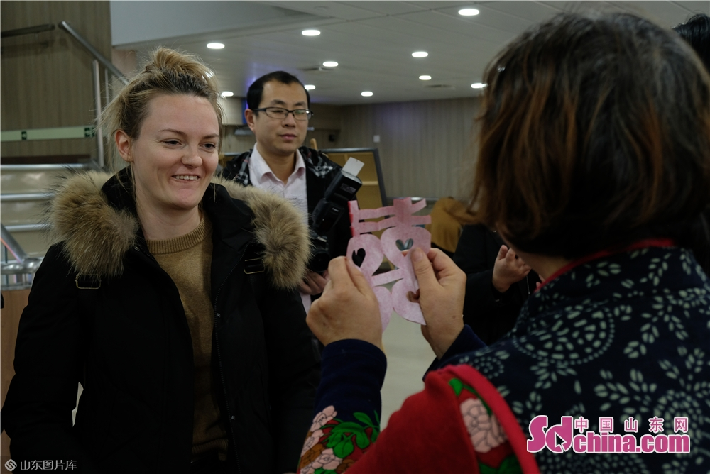 A craftsman teaches foreigners how to make paper cutting works A foreigner learn embroidery on the Fuxing cruise in Yantai, Shandong Province on Dec. 27, 2017. The New Year celebrations of Yantai kicked off here on Friday.