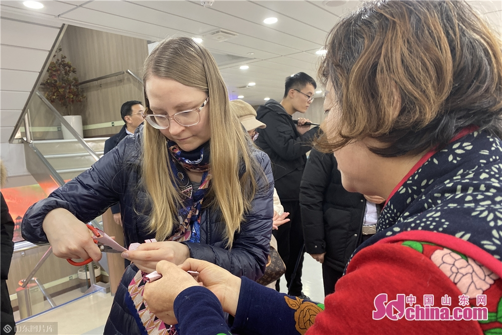 A foreigner learns paper cutting on the Fuxing cruise in Yantai, Shandong Province on Dec. 27, 2017. The New Year celebrations of Yantai kicked off here on Friday.<br/>