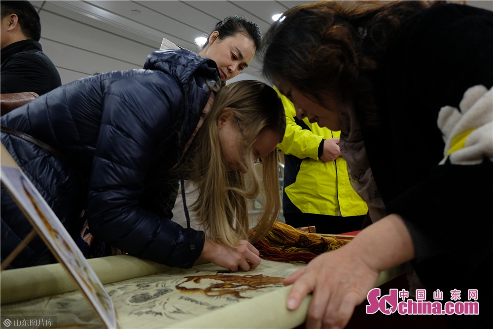 A foreigner learn embroidery on the Fuxing cruise in Yantai, Shandong Province on Dec. 27, 2017. The New Year celebrations of Yantai kicked off here on Friday.<br/>