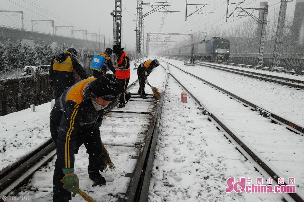 <br/>  潍坊东站铁路工作人员清理铁道积雪,保障铁路通行。<br/>