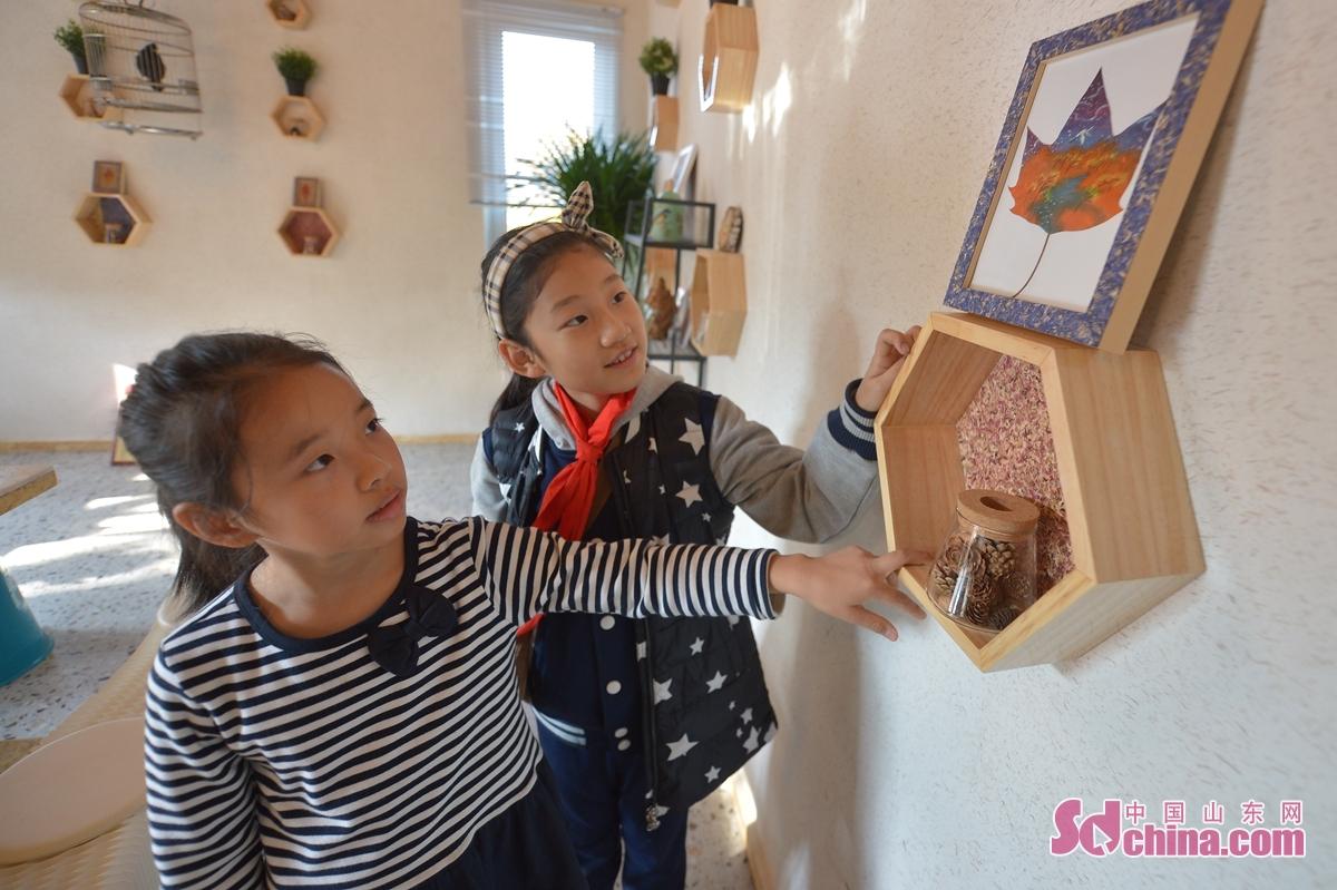 <br/>  11月15日,两名小朋友在青岛市&ldquo;公益科普驿站&rdquo;首场活动上观赏树叶画。