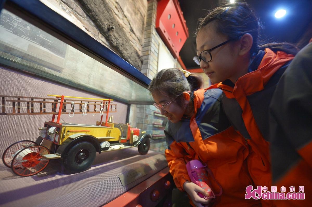 학생은 전시관에 청도 백년 전 소방차 모델을 구경한다.<br/>