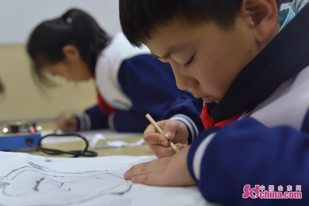 <br/>  12月1日,一名学生在描绘自己设计的图案。<br/>