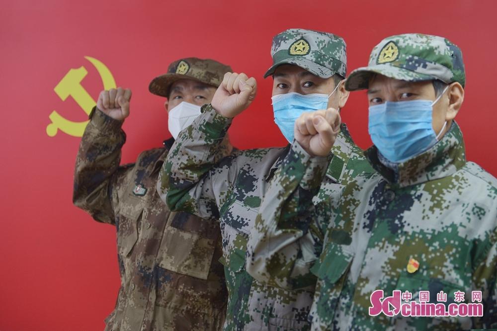 <br/>  三名党员退伍军人在党旗下重温入党誓词。<br/>