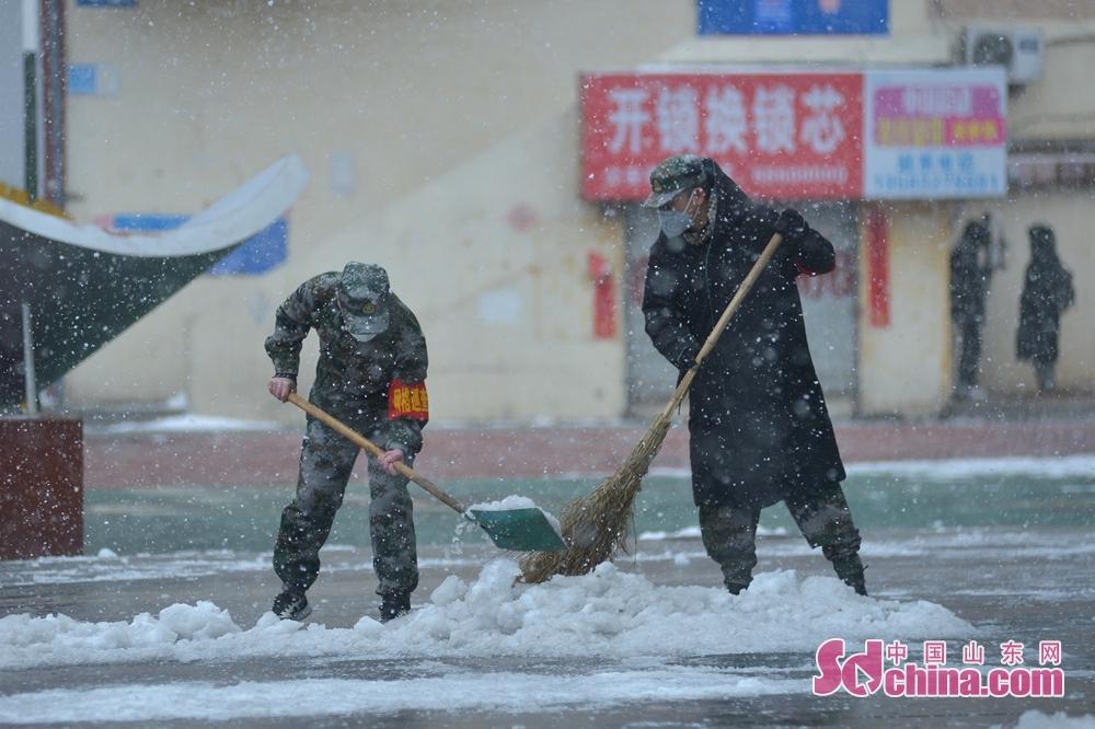 <br/>  两名党员志愿服务队的退伍军人顶风冒雪清理街道。<br/>