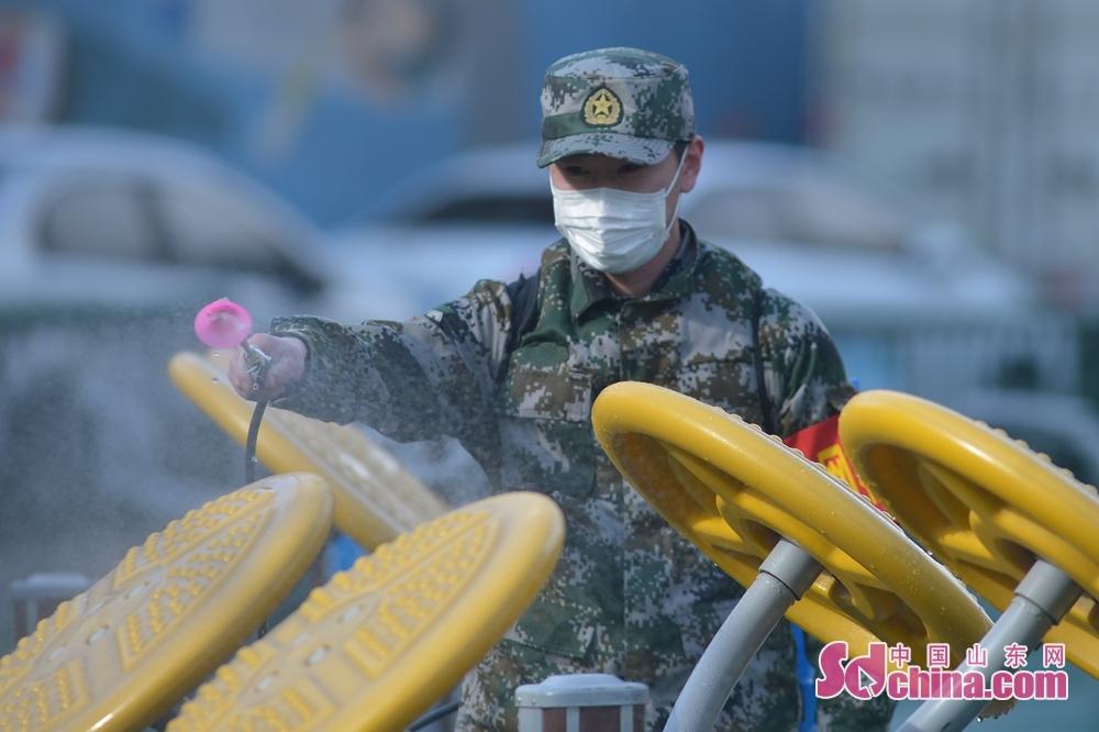 <br/>  一名党员志愿服务队的退伍军人对社区体育设施进行消毒作业。<br/>