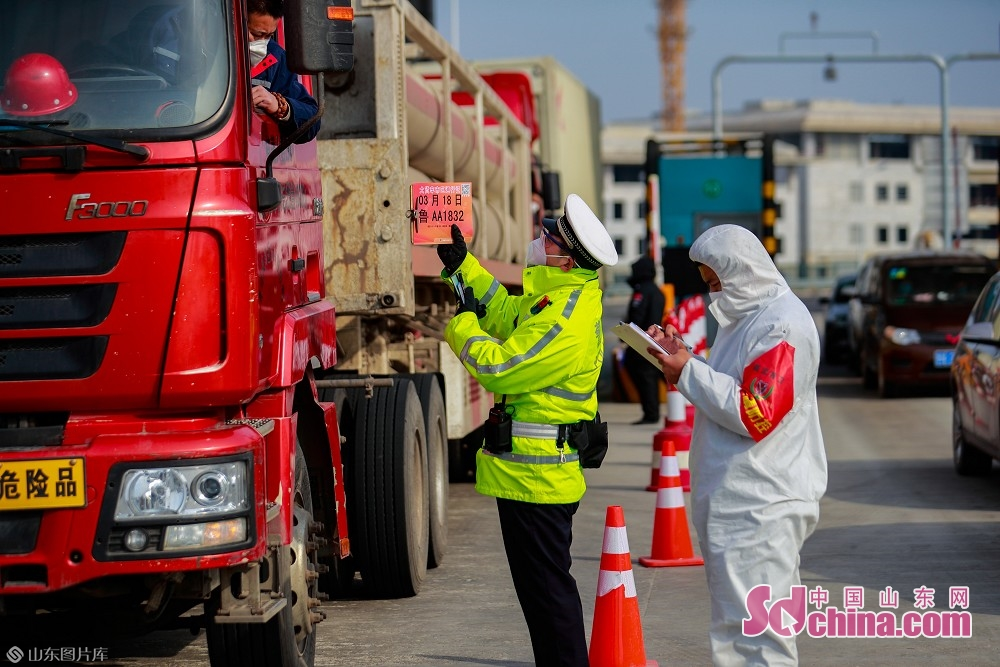 A traffic police and a medical worker inspect vehicles at the exit of Jinan West Toll Station in Jinan, capital of Shandong Province, on Feb. 19, 2020. Recently, Jinan sent police on duty 24 hours a day to guard the city&rsquo;s 45 highway toll gates and 28 intercity checkpoints on the national roads and provincial roads to prevent the spread of the epidemic.<br/>
