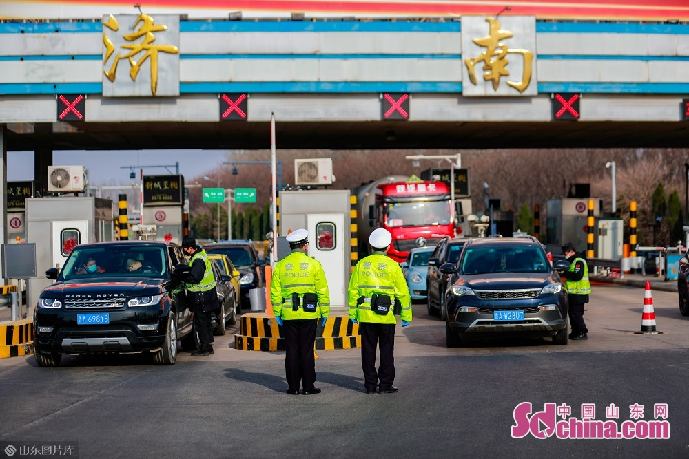 Traffic policemen inspect vehicles at the exit of Jinan West Toll Station in Jinan, capital of Shandong Province, on Feb. 19, 2020. Recently, Jinan sent police on duty 24 hours a day to guard the city&rsquo;s 45 highway toll gates and 28 intercity checkpoints on the national roads and provincial roads to prevent the spread of the epidemic.<br/>