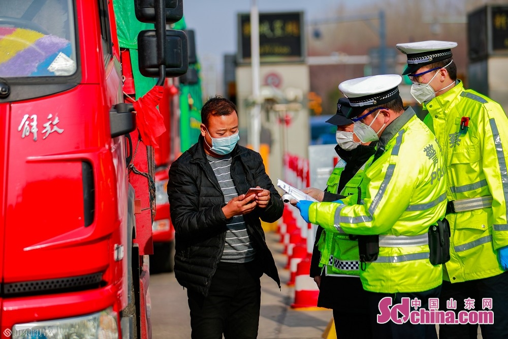 Three traffic policemen inspect vehicles at the exit of Jinan West Toll Station in Jinan, capital of Shandong Province, on Feb. 19, 2020. Recently, Jinan sent police on duty 24 hours a day to guard the city&rsquo;s 45 highway toll gates and 28 intercity checkpoints on the national roads and provincial roads to prevent the spread of the epidemic.<br/>
