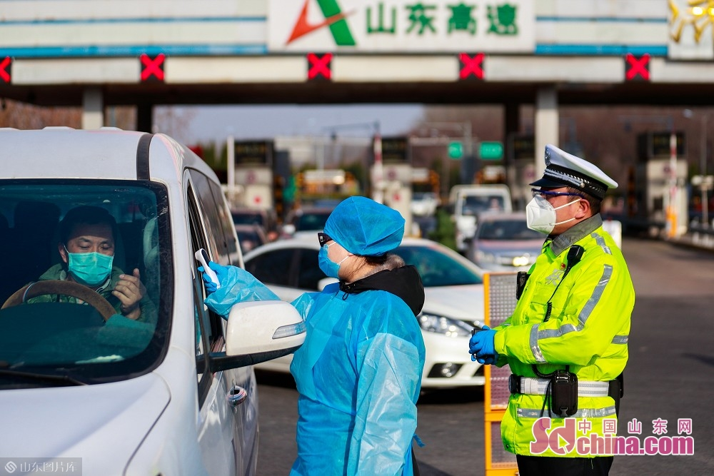 A traffic police and a medical worker inspect vehicles at the exit of Jinan West Toll Station in Jinan, capital of Shandong Province, on Feb. 19, 2020. Recently, Jinan sent police on duty 24 hours a day to guard the city's 45 highway toll gates and 28 intercity checkpoints on the national roads and provincial roads to prevent the spread of the epidemic.