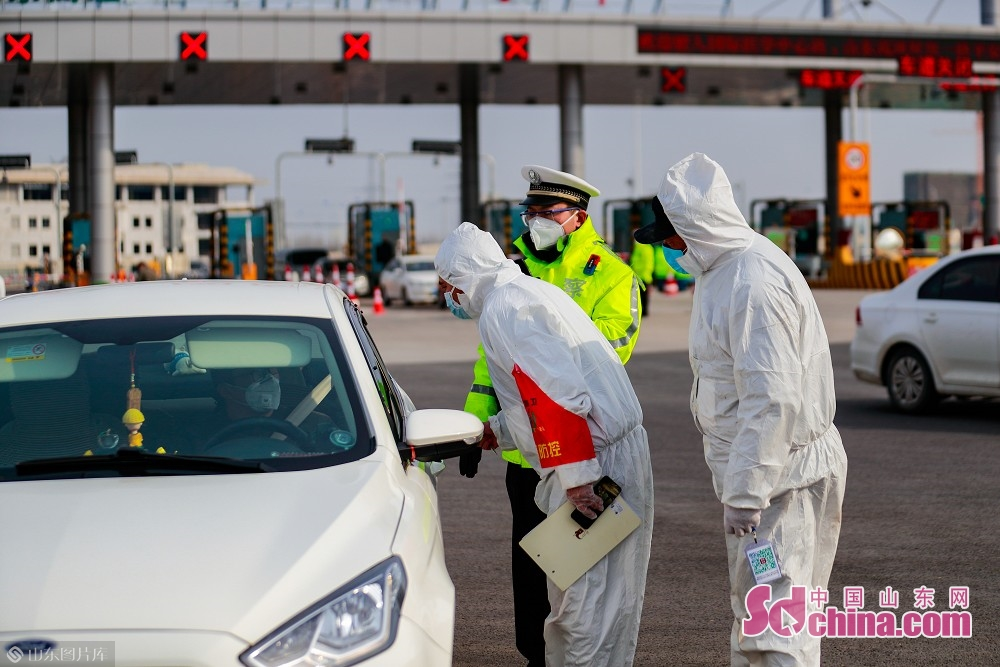A traffic police and two medical workers inspect vehicles at the exit of Jinan West Toll Station in Jinan, capital of Shandong Province, on Feb. 19, 2020. Recently, Jinan sent police on duty 24 hours a day to guard the city&rsquo;s 45 highway toll gates and 28 intercity checkpoints on the national roads and provincial roads to prevent the spread of the epidemic.<br/>
