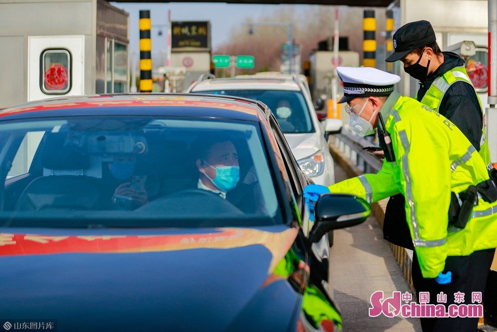 Two traffic policemen inspect vehicles at the exit of Jinan West Toll Station in Jinan, capital of Shandong Province, on Feb. 19, 2020. Recently, Jinan sent police on duty 24 hours a day to guard the city&rsquo;s 45 highway toll gates and 28 intercity checkpoints on the national roads and provincial roads to prevent the spread of the epidemic.<br/>