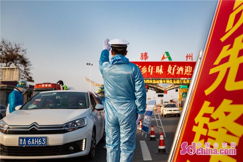 <br/>  山东滕州交警配合防疫部门对车辆进行拦截检查。(摄影 张辉)<br/>