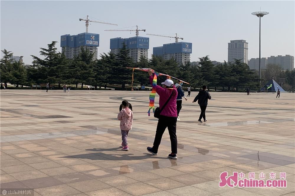 <br/>  家长带着小朋友在人民广场放起了风筝。<br/>