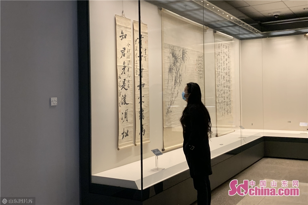 A visitor views calligraphy works in the City Museum in Weifang, east China's Shandong Province on March 25, 2020. Weifang City Library, Wiefang City Museum, Weifang City Art Gallery, Weifang Shihu Garden Museum, and Weifang Kite Museum opened to the public from Wednesday.<br/>