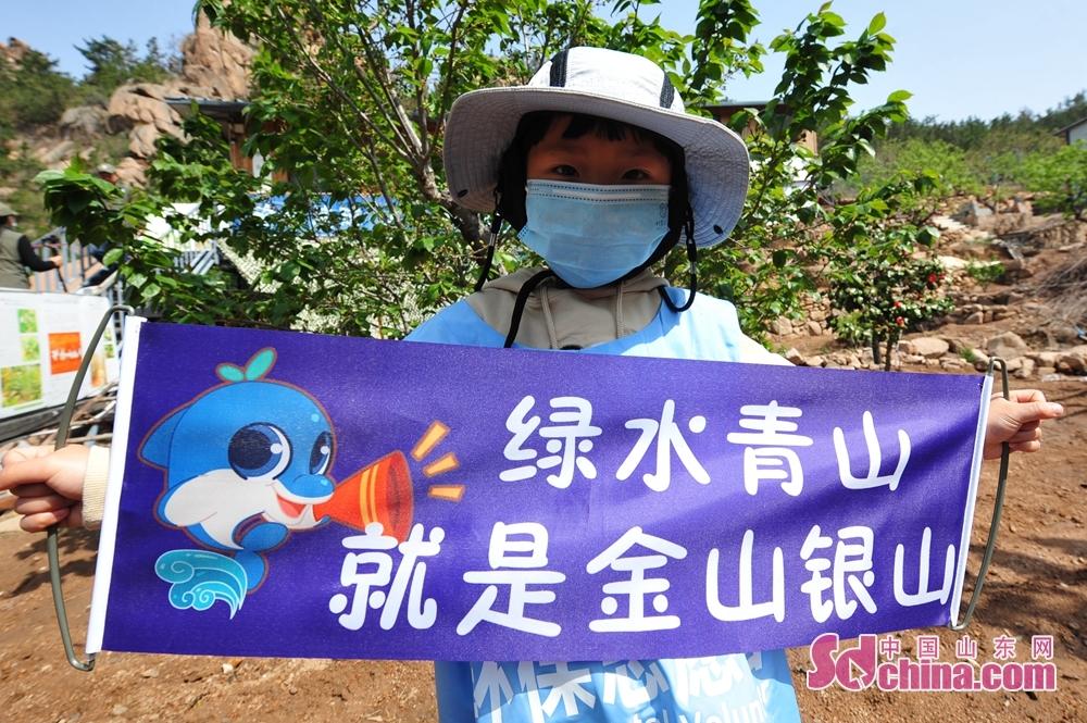 <br/>  4月17日,在山东省青岛市城阳区野生动植物保护协会科普基地,一名小志愿者展示宣传条幅。<br/>