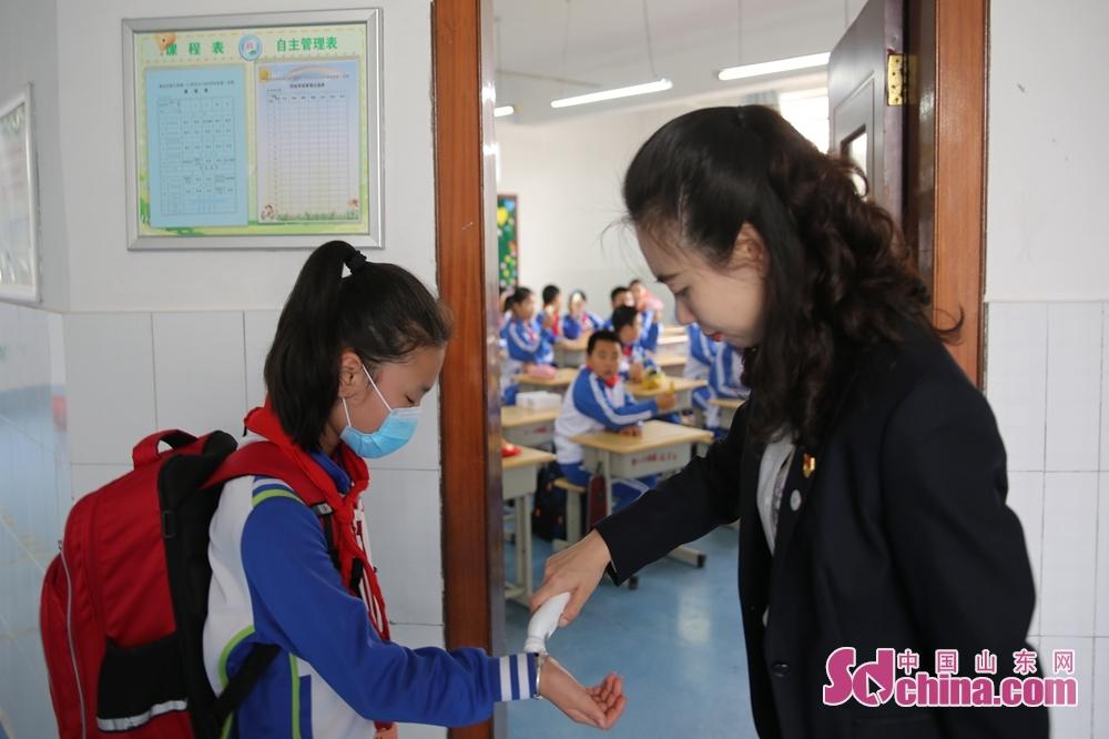 <br/>  5月25日,青岛西海岸新区香江路第一小学的老师在给学生进行二次测温。<br/>