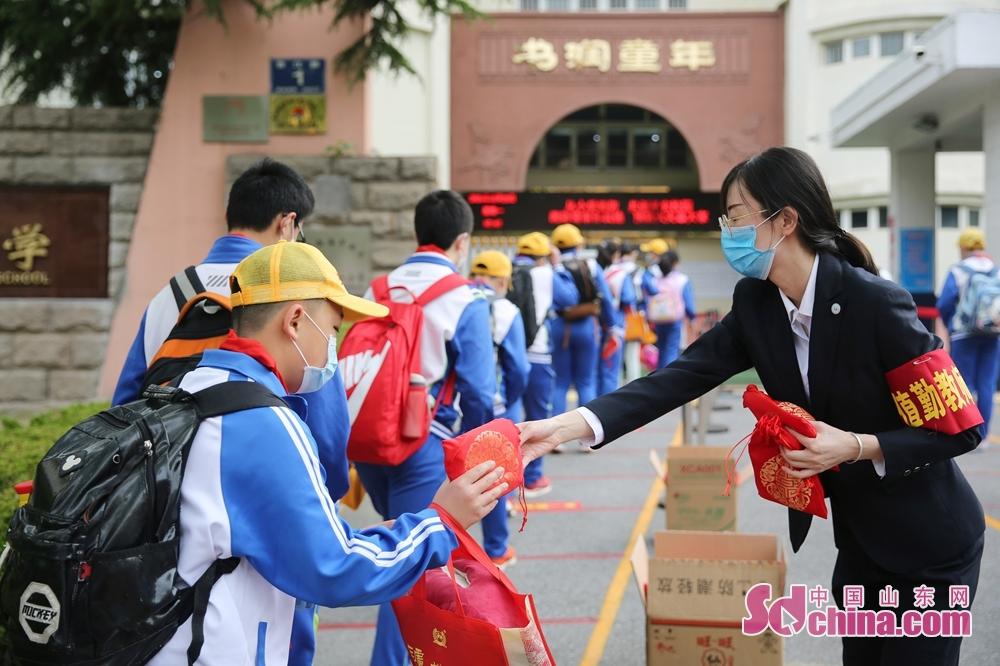 <br/>  5月25日,青岛西海岸新区香江路第一小学的老师在给每一名学生发放&ldquo;健康复学大福包&rdquo;,里边有口罩、消毒湿巾、棒棒糖等。<br/>