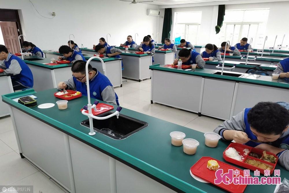 <br/>  济南第十三中学学生中午保持安全距离用餐。<br/>