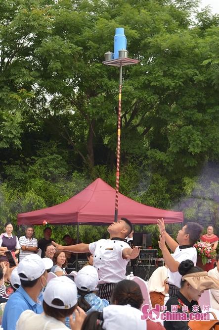 <br/>  在青岛市城阳区韩家民俗村举办的端午主题活动上,一名杂技演员现场进行&ldquo;快乐厨师&rdquo;表演。<br/>