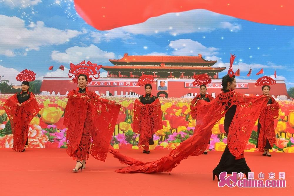 <br/>  在青岛市城阳区韩家民俗村举办的端午主题活动上,村民进行剪纸走秀表演。