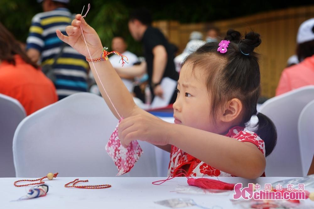 <br/>  在青岛市城阳区韩家民俗村举办的端午主题活动上,一名小朋友学习缝制香包。<br/>