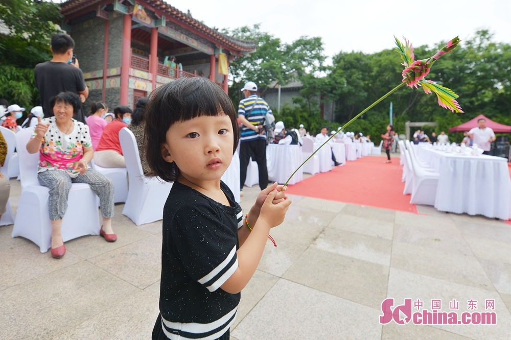 <br/>  在青岛市城阳区韩家民俗村举办的端午主题活动上,一名小朋友手持草编蜻蜓观看节目表演。<br/>