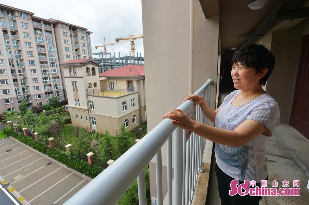<br/>  7月23日,在山东省青岛市李沧区文昌路820号,一名领取了保障性住房钥匙的居民在走廊上欣赏小区景色。<br/>