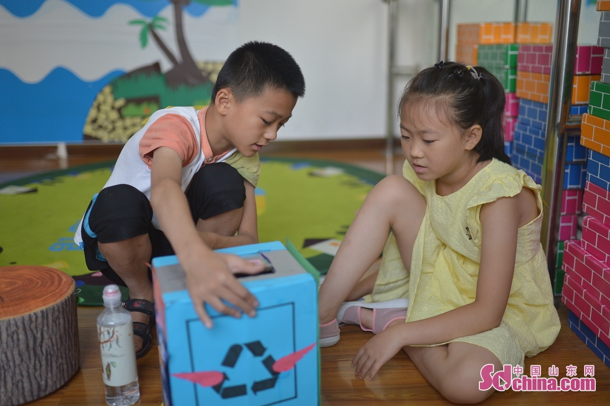 <br/>  7月29日,来自青岛洮南路小学(左)和青岛芙蓉山小学的学生共同体验制作垃圾分类箱。<br/>