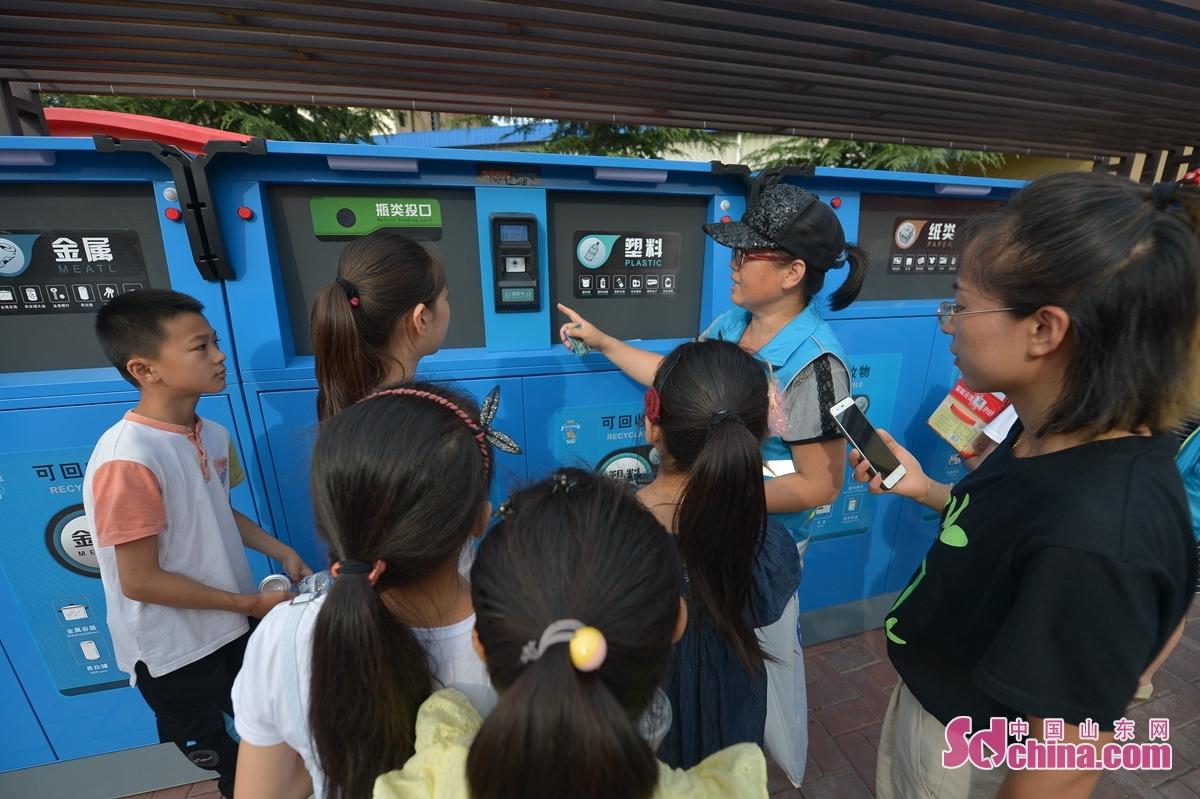 <br/>  7月29日,青岛市镇江路街道的工作人员为孩子们讲解智能垃圾分类设备。