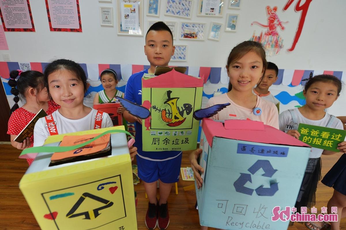 <br/>  7月29日,来自青岛洮南路小学等学校的孩子们展示自己绘制的垃圾分类箱。<br/>