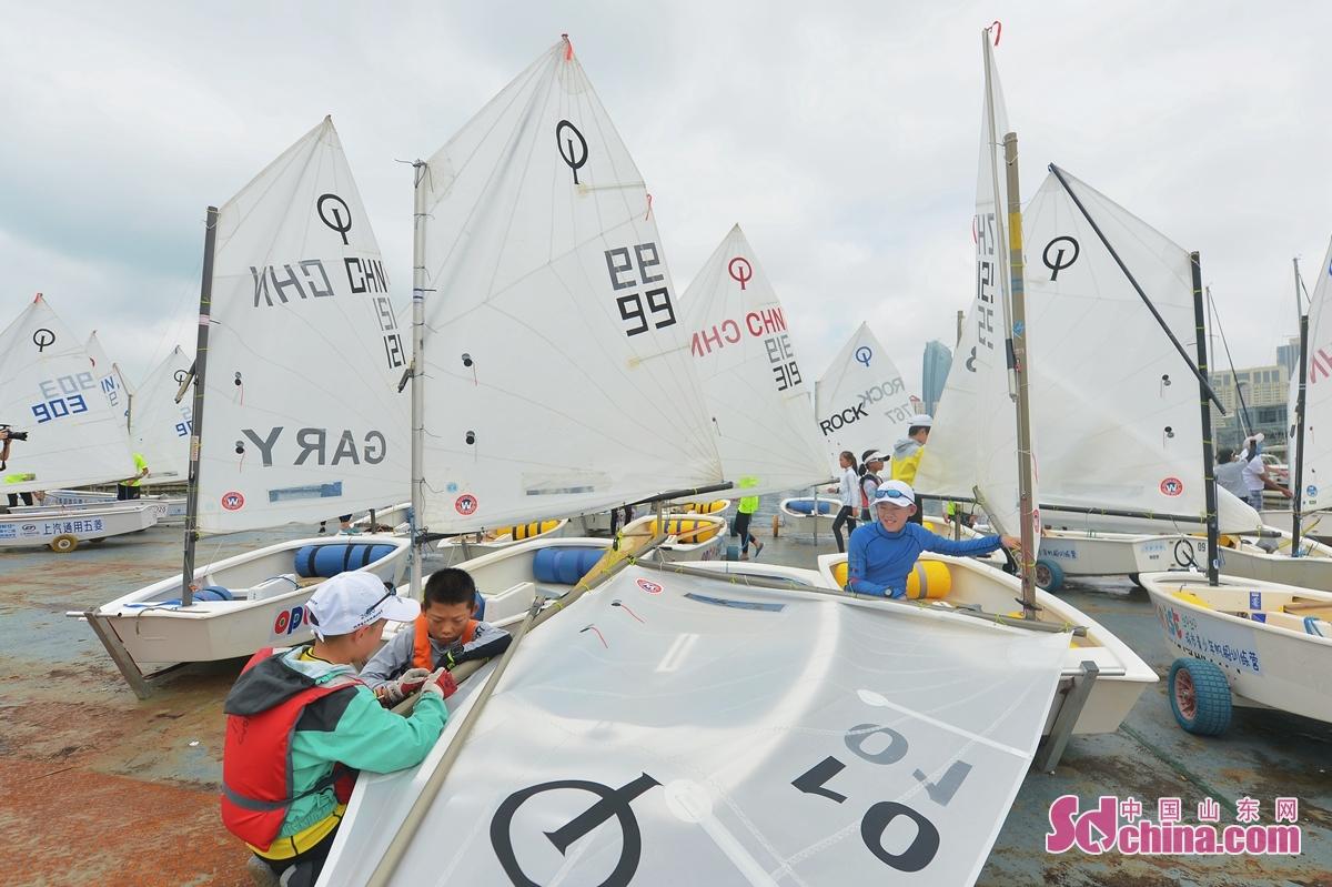 <br/>  8月8日,参加青岛国际帆船周&middot;海洋节国际OP帆船营的小选手在赛前检查船只。<br/>