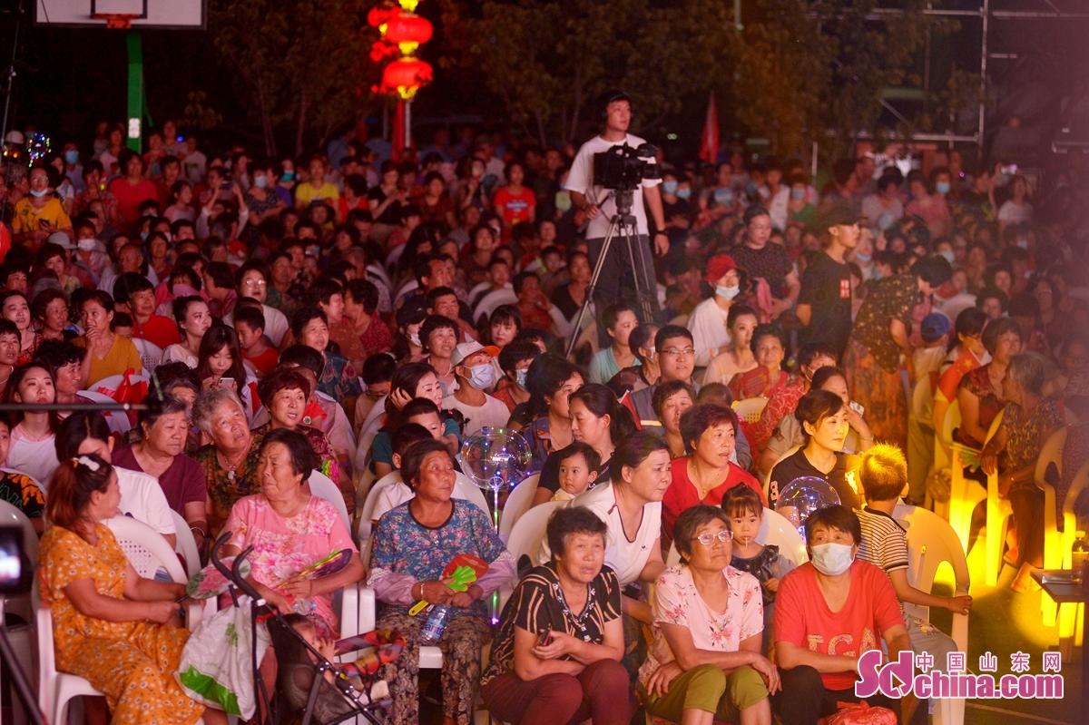 <br/>  8月28日,社区居民在青岛城阳红岛街道第十九届市民文化艺术节暨孝亲节颁奖典礼上观看晚会节目表演。