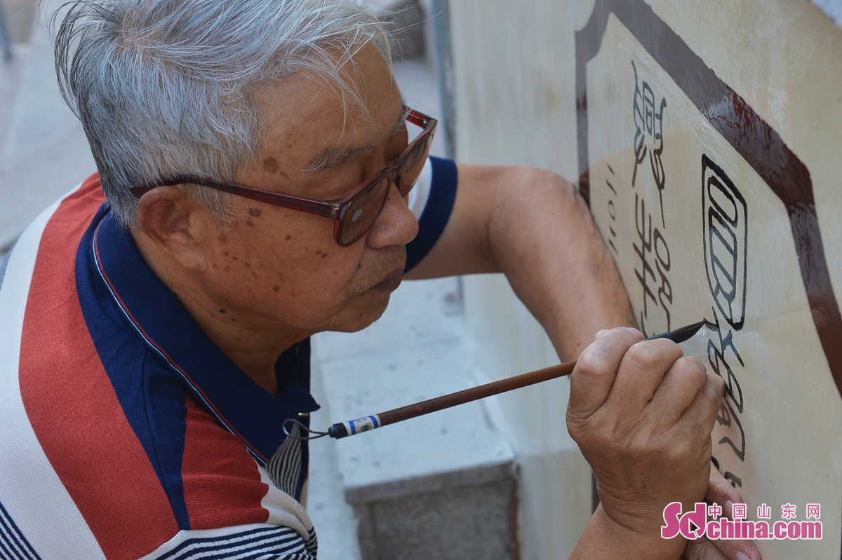 A calligrapher writes on a wall on No.2 Yan&rsquo;an Road in Qingdao, a coastal city of east China&rsquo;s Shandong Province, Sept. 24, 2020. Main streets, walls and buildings in No.2 Yan&rsquo;an Road Community are decorated with calligraphy and colored drawing to celebrate the upcoming Mid-Autumn Festival and the National Day holiday. (Photo by Wang Haibin)<br/>